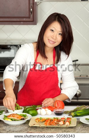 Young Pretty Asian Woman Preparing Green Healthy Food in Kitchen - stock photo