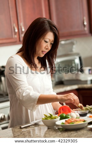 Young Pretty Asian Woman Preparing Healthy Food in Kitchen - stock photo