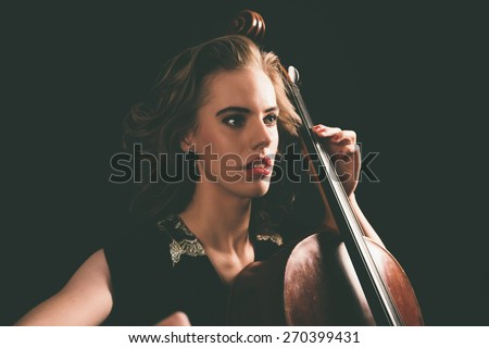 Young pretty aspiring female musician playing a cello during a recital at a music academy, low angle close up view of her face and hands