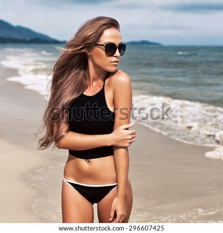 Young pretty beautiful blonde sexy woman posing outdoor on the beach in warm weather on tropic island on vacation and have fun in black bikini on ocean seashore  - stock photo