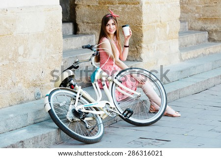 Young pretty blond-brown girl sitting on concrete stairs with a cup of coffee and looking toward, with vintage bicycle, in an old European city  - stock photo