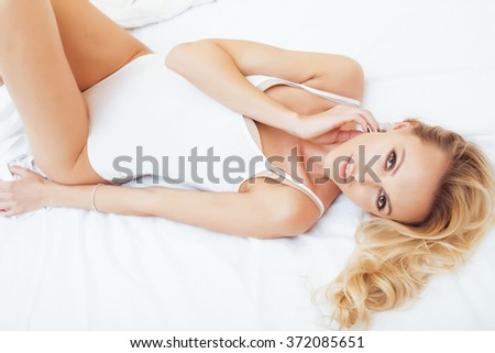 young pretty blond woman in bed covered white sheets smiling cheerful sexy look close up, happy morning  - stock photo