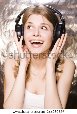 young pretty blond woman listening music and singing in big earphones isolated on white - stock photo