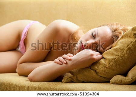 Young pretty blond woman sleeping on couch - stock photo