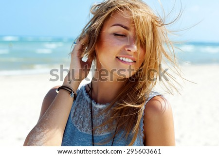 Young pretty blonde fashion girl sensual portrait posing outdoor in summer having fun on fresh air wind blowing hairs smiling  - stock photo