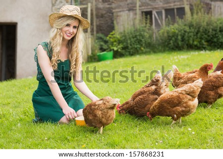 Young pretty blonde feeding her chickens smiling at camera kneeling on the grass