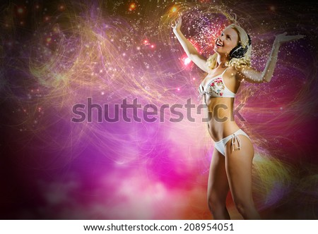 Young pretty blonde in bikini dancing with headphones on head