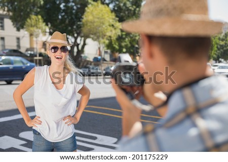 Young pretty blonde posing for her boyfriend on a sunny day in the city - stock photo