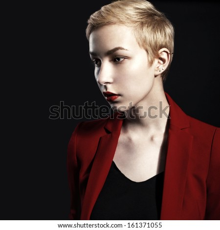 Young pretty blonde posing in studio with red lips and jacket on black background with copyspace - stock photo