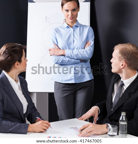 Young pretty bossy businesswoman talking with her colleagues - stock photo
