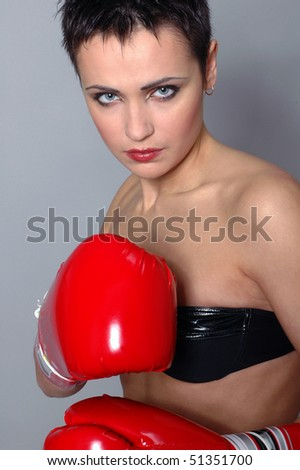 Young pretty boxer woman in red gloves - stock photo