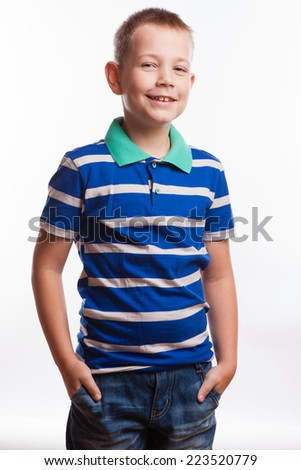 Young pretty boy posing at studio as a fashion model. Photo of preschooler 7 years old over white background - stock photo