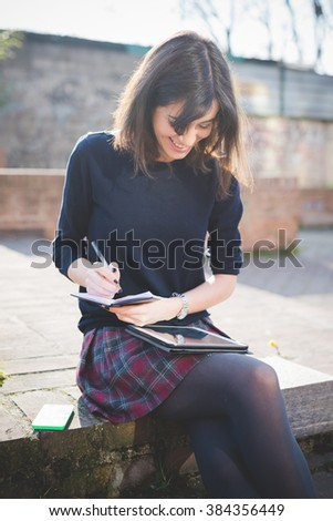young pretty brown hair woman in town using writing down on a diary and using tablet, looking downward, smiling - multitasking, technology, working concept - stock photo