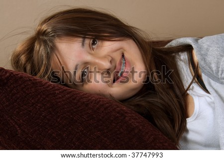 Young pretty brunette hispanic teenage girl with messy hair smiling laying on pillow with braces - stock photo