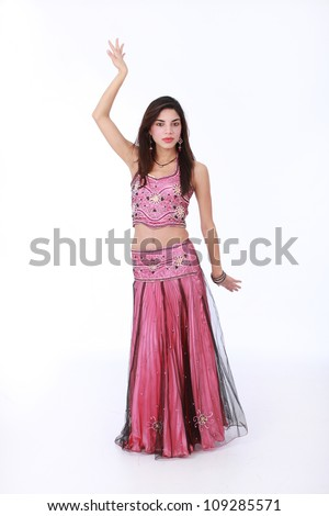 Young pretty brunette Muslim woman wearing traditional Indian cultural dress in pink satin and beaded embroidery and elaborate earrings with jewels and beads.