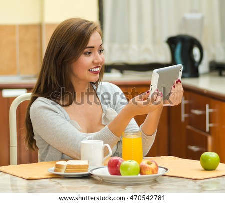 Young pretty brunette sitting by breakfast table looking at tablet screen, fruits, juice and coffee placed in front, hostel environment