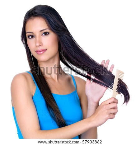 Young pretty brunette woman combing her beautiful long hair - isolated on white background - stock photo