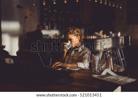 young pretty brunette woman eat chocolate in cafe, using smartphone and laptop touch screen display, sweet food, tasty breakfast, close up portrait, hipster girl, fanny, drink coffee