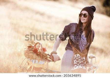 Young pretty brunette woman posing on the nature with bike in summer sunshine. Fashion portrait.  - stock photo