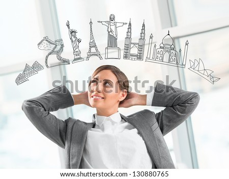 Young pretty business woman dreaming about vacation and her trip to famous touristic destination. Architecture symbols overhead - stock photo