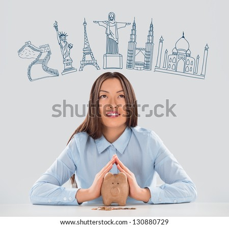Young pretty business woman dreaming about vacation and saving money with piggy bank for her trip to famous touristic destination. Architecture symbols overhead