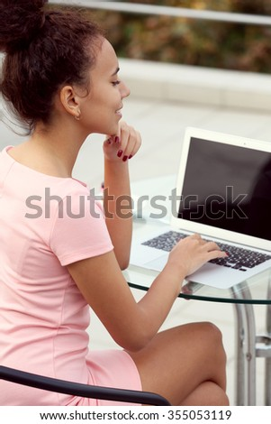 Young pretty business woman in pink dress with laptop at summer terrace