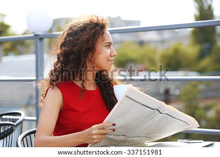 Young pretty business woman in red dress reads newspaper at the restaurant's terrace - stock photo
