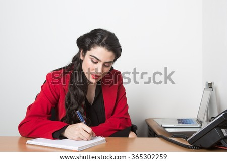 Young pretty business woman in the office  taking notes