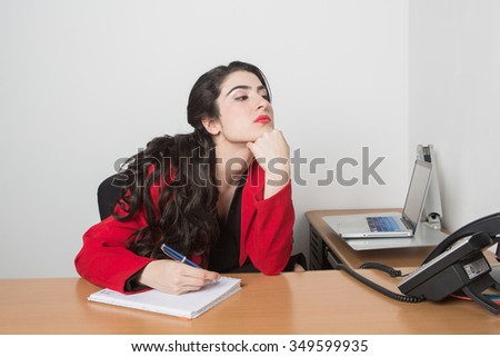 Young pretty business woman in the office taking notes looking bored. She is wearing a black blouse and a red Jacket