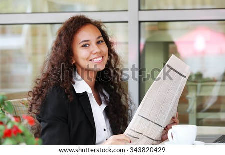 Young pretty business woman reads newspaper in the restaurant's terrace - stock photo