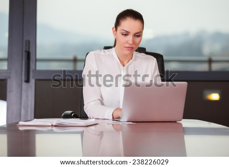 Young pretty business woman with laptop in the office - stock photo