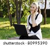 Young pretty business woman with laptop sitting on the bench in a park. - stock photo