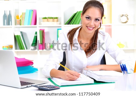 Young pretty business woman with notebook in office - stock photo