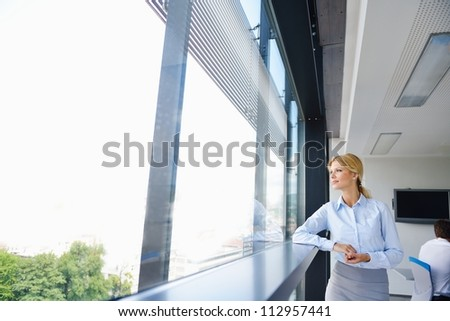 Young pretty business woman with notebook in the bright modern office indoors - stock photo