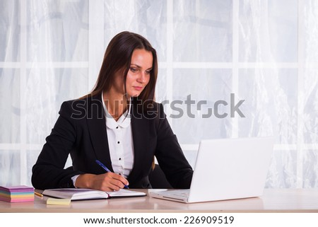 Young pretty business woman with notebook in the office. - stock photo