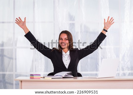 Young pretty business woman with notebook in the office.Successful business woman with arms up - isolated over a white background - stock photo