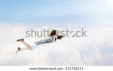 Young pretty businesswoman flying in blue sky - stock photo