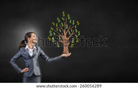 Young pretty businesswoman holding drawn dollar in hand - stock photo