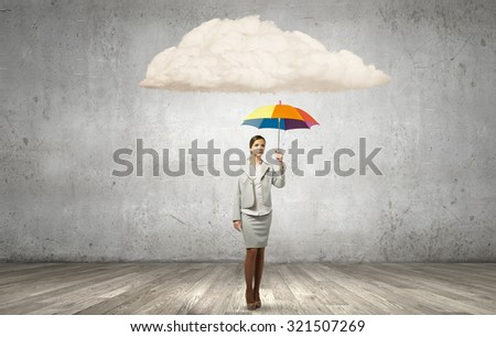 Young pretty businesswoman in suit with colorful umbrella - stock photo