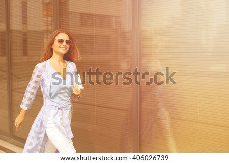 Young pretty businesswoman in sunglasses smiling and walking near business building. She is is a hurry to the meeting with her partners. - stock photo