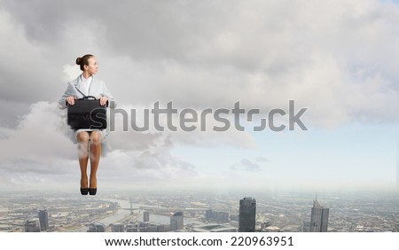 Young pretty businesswoman sitting on cloud high above city