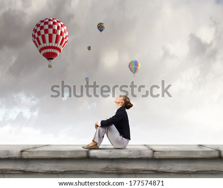 Young pretty businesswoman sitting on top of building with colorful balloons flying above - stock photo