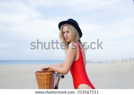 Young pretty caucasian female dressed in fashionable swimwear posing for the camera while standing on the beach with retro bicycle against sea and sky background with copy space area for your content - stock photo