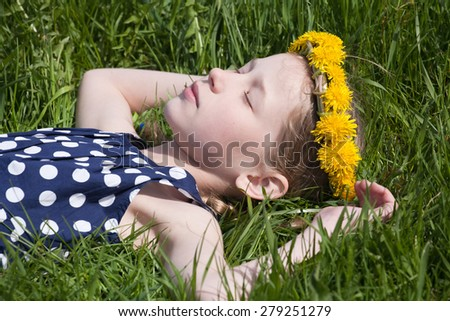 young pretty caucasian girl in yellow dandelions garland lying and sleeping on green grass - stock photo