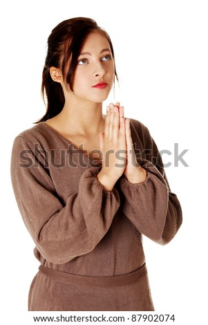 Young pretty caucasian girl standing and praying. Isolated on white. - stock photo