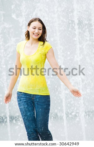 young pretty caucasian lady having fun at an outdoor water fountain - stock photo