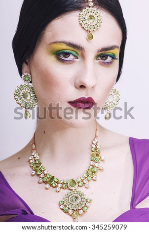 young pretty caucasian woman like indian in ethnic jewelry close up on white, bridal makeup