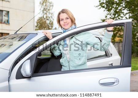 Young pretty Caucasian woman standing behind a car with opened door - stock photo