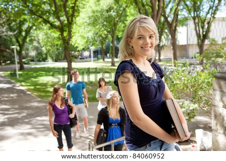 Young pretty college student looking at the camera with a smile - stock photo