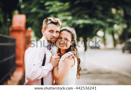 Young pretty colored portrait of young couple in love posing in evening in city and having fun together - stock photo